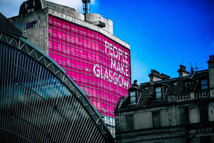 Glasgow buildings with People make Glasgow sign