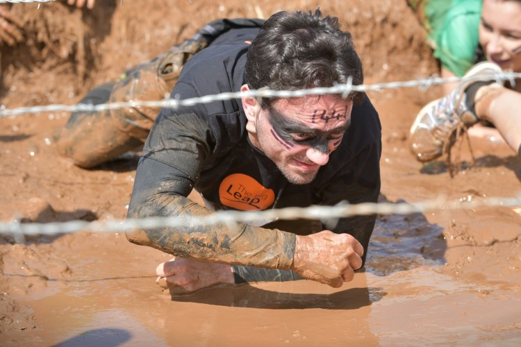 Man crawling through mud under barbed wire