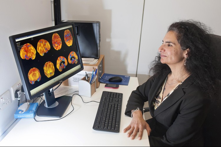 Professor Sharon Abrahams looking at a screen showing brain scan images