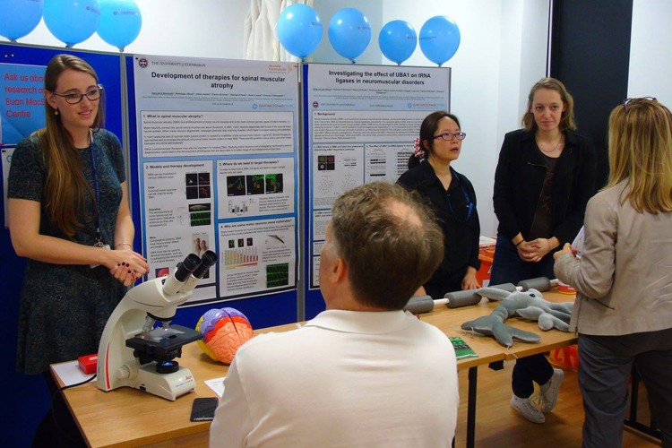 researchers at a display stand chatting about their work with the public