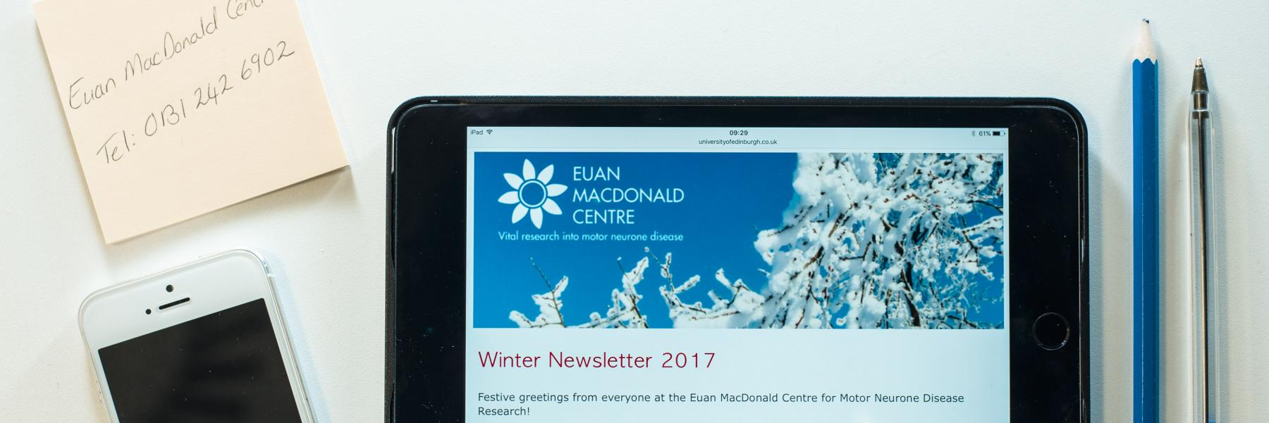 office items on a table with a tablet computer showing the Euan MacDonald Centre newsletter