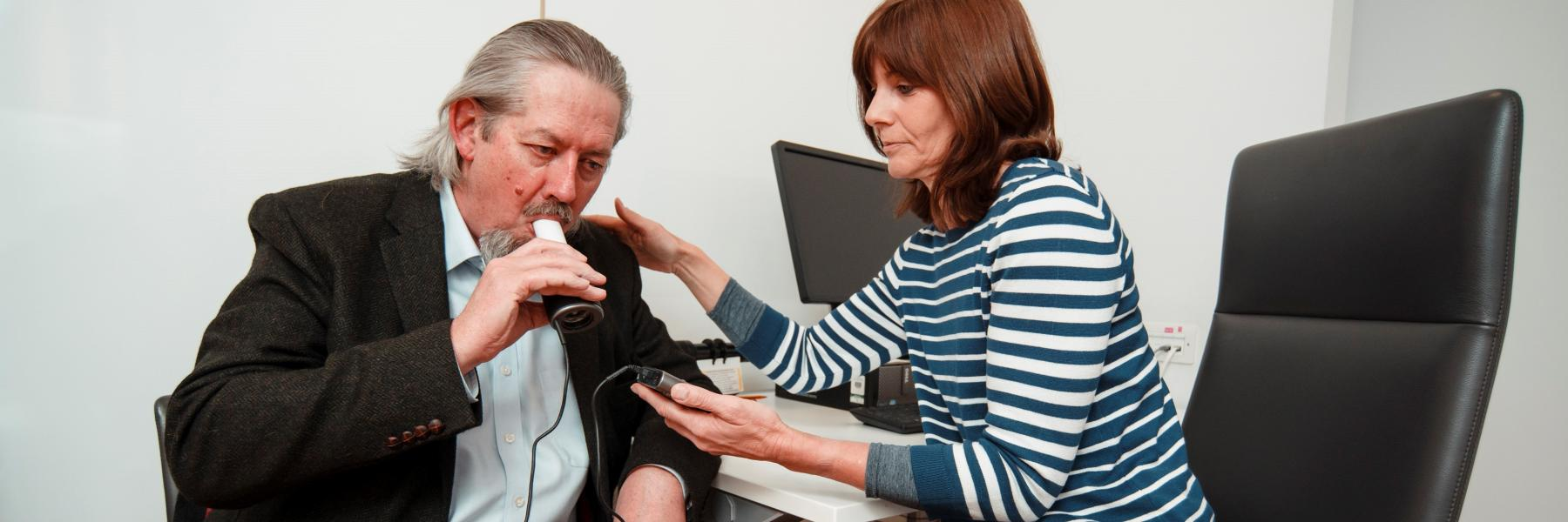 Man doing a breathing test sat at a desk with a female reseacher.